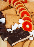 Various sweets. Various cookies and  chocolate candy with  sugar on wooden surface Royalty Free Stock Image