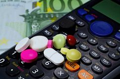 Various tablets on calculator and euro money. Pills, calculator and money. Various tablets on calculator and euro money Royalty Free Stock Photo