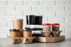 Various takeout containers on table against white brick wall. Food delivery service stock photography