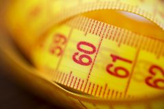 Various tape measure as background. A yellow measuring tape as background. Measuring tape of yellow color for measurement of lengt stock photography