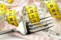 Various tape measure and fork. Diet concept Royalty Free Stock Photography