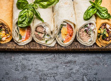 Various of tasty tortilla wraps on dark rustic background, top view, border. Stock Images