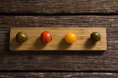 Various tomatoes arrange in wooden tray Stock Photos