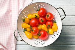 Various tomatoes in colander Stock Images