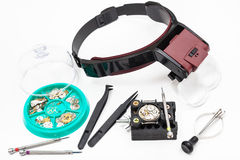 Various tools with head-mounted magnifier. Watchmaker workshop - various tools with head-mounted magnifier and spare parts for repairing mechanical watch on Stock Photos