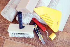 Various tools for home repair and rolls of wallpaper Stock Photo