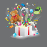Toys burst from present box in black background Royalty Free Stock Photos