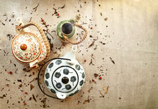 3 various traditional ceramic teapots on a canvas background. With copy space. Group of cute steaming clayware pots with hot tea among tea leaves and berries stock image
