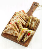 Various triangle sandwiches on wooden board Stock Photos