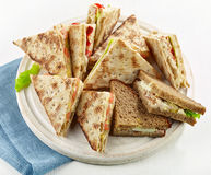 Various triangle sandwiches on wooden board Stock Photography