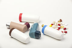 Various types of asthma inhalers and some pills on white Royalty Free Stock Image