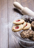 Various types of biscuits on glass tray next to a roller on wooden table. Royalty Free Stock Photos