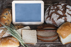 Various types of bread with a blackboard on a wooden table Stock Photos