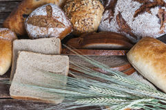 Various types of bread on a wooden table Royalty Free Stock Image