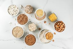 Various types cereal grains groats. Selection various types cereal grains groats  in different bowl on white marble background, copy space top view Stock Images