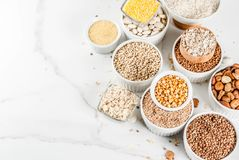 Various types cereal grains groats. Selection various types cereal grains groats  in different bowl on white marble background, copy space top view Stock Photos