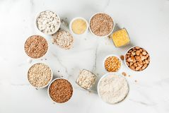 Various types cereal grains groats. Selection various types cereal grains groats  in different bowl on white marble background, above frame space for text Royalty Free Stock Photography