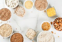 Various types cereal grains groats. Selection various types cereal grains groats  in different bowl on white marble background, above frame copy space Royalty Free Stock Image