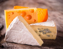 Various types of cheese. On wooden background stock image
