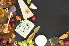 Various types of cheese. On black cutting board with copy space stock photography