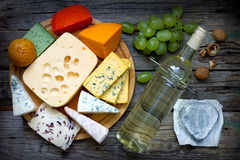 Various types of cheese with bottle of wine on old retro boards still life Royalty Free Stock Image