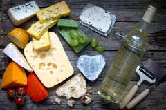 Various types of cheese with bottle of wine on old retro boards still life Stock Photography