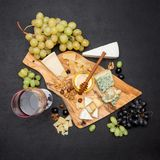 Various types of cheese - brie, camembert, roquefort and cheddar and wine stock photos