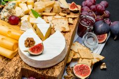 Various types of cheese - brie, camembert, roquefort and cheddar on wooden board. Various types of cheese - brie, camembert, roquefort and cheddaron wooden royalty free stock image