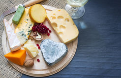 Various types of cheese on cutting board Royalty Free Stock Images