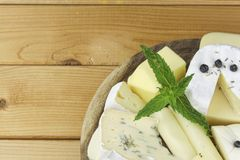 Various types of cheese on a cutting board Stock Images