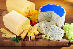 Various types of cheese on cutting board Stock Photos
