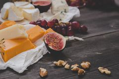 Various types of cheese with fruits and nuts on the wooden dark table. Selective focus.  Stock Photography