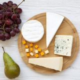 Various types of cheese with fruits on a white wooden surface. Food for wine, top view. Flat lay. From above.  royalty free stock images