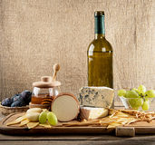 Various types of cheese, grapes, honey,  bottle of wine Stock Photo