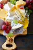 Various types of cheese with grapes, honey and walnuts on cutting board Royalty Free Stock Image