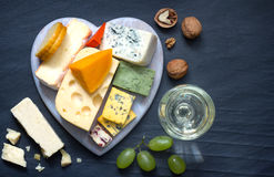 Various types of cheese on heart with glass of wine Royalty Free Stock Photos