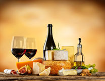 Various types of cheese with red wine. Various types of cheese, glasses and bottle of red wine placed on wooden table, copyspace for text. Abstract brown blur royalty free stock images