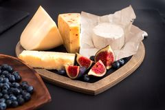 various types of cheese on rustic wooden table, goat cheese, chevre, grana padana, fig, blueberry royalty free stock photo