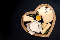 various types of cheese on rustic wooden table, goat cheese, chevre, grana padana, fig, blueberry stock photo