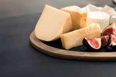 various types of cheese on rustic wooden table, goat cheese, chevre, grana padana, fig, blueberry royalty free stock image