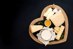 Various types of cheese on a stand in the shape of a heart, concept elegant life and love cheese, top view. Various types of cheese in wooden box on white wooden royalty free stock images