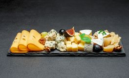 Various types of cheese on stone board royalty free stock photo