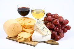 Various types of cheese, wine, grapes and crackers Stock Photos