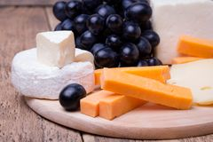 Various types of cheese on wooden background. Various types of cheese with grape on wooden background Stock Image