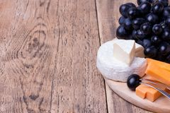 Various types of cheese on wooden background. Cheese knife and various types of cheese on wooden background with copyspace Royalty Free Stock Photos
