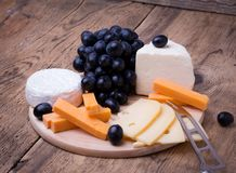 Various types of cheese on wooden background. Cheese knife and various types of cheese on wooden background with copyspace Stock Image