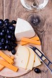 Various types of cheese on wooden background. Cheese knife, grapes and various types of cheese on wooden background with copyspace Royalty Free Stock Photos