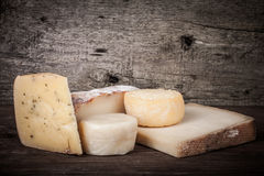 Various types of cheese on a wooden background. tinted Stock Image