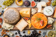 Various types of cheese. On wooden cutting board, top view stock photography