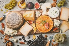 Various types of cheese. On wooden cutting board, top view royalty free stock image